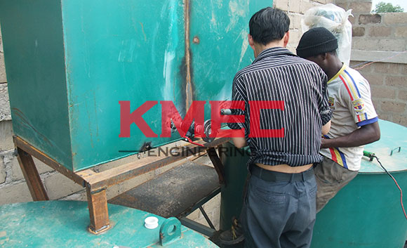 workers   are welding hot water tank outlet valve